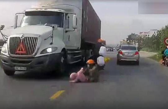 Clip bị ô tô quệt văng xuống đường, mẹ cứu con nhỏ tránh bị container cán chết