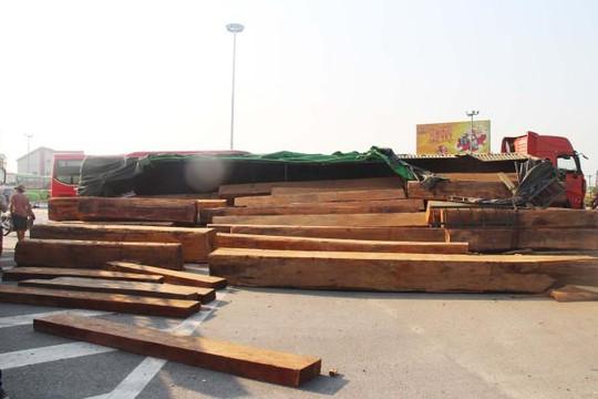 Xe đầu kéo bị lật, hàng chục khúc gỗ lớn đổ tràn ra quốc lộ