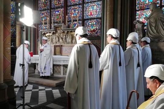 Các linh mục đội mũ bảo hiểm tổ chức thánh lễ tại Nhà thờ Đức Bà Paris